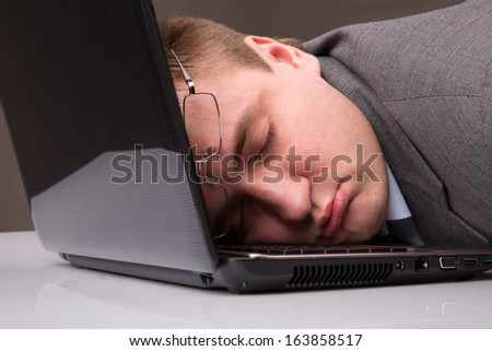 Office worker asleep on a laptop keyboard - stock photo