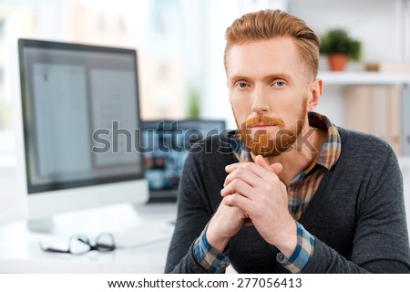 Office worker at his desk. Thoughtful young bearded man keeping hands clasped and looking at camera while sitting at his working place - stock photo