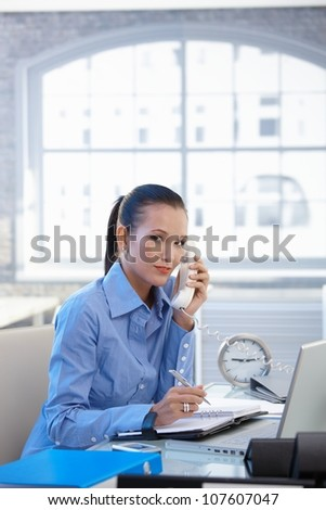 Office worker girl taking landline call, writing notes, looking at camera, smiling. - stock photo