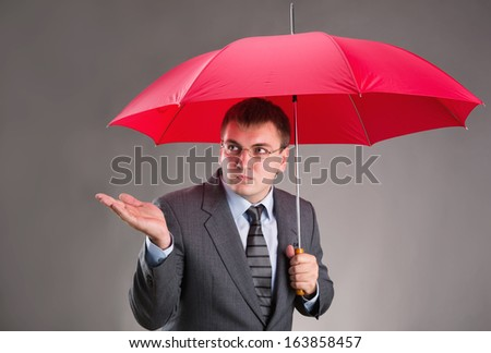 Office worker hiding under an umbrella and waiting for the rain - stock photo