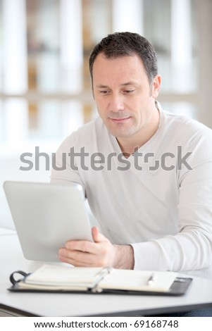 Office worker in the office using electronic tab - stock photo