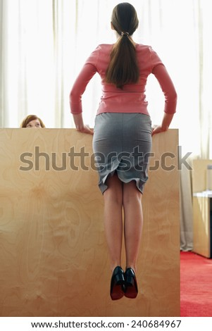 Office Worker Jumping near Coworkers Cubicle - stock photo