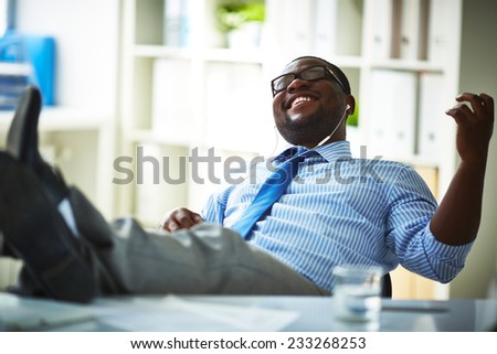 Office worker listening to music at workplace - stock photo