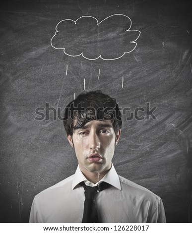 Office worker with a cloud drawn on a black board over him - stock photo