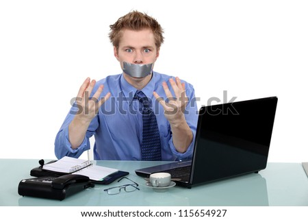 Office worker with his mouth taped shut - stock photo