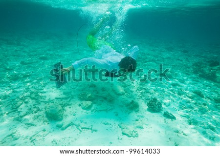 Office worker with keyboard swimming underwater in formal clothes with red tie - stock photo