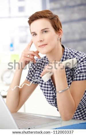 Office worker woman thinking with landline phone handheld. - stock photo