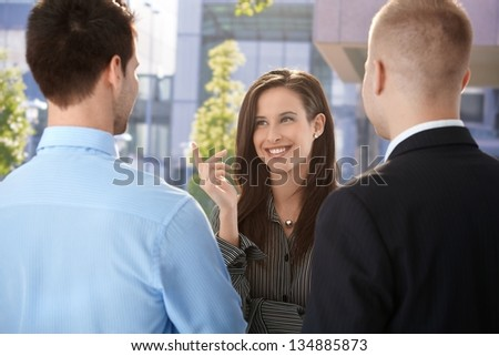 Office workers chatting at break time, standing outside of office building. - stock photo