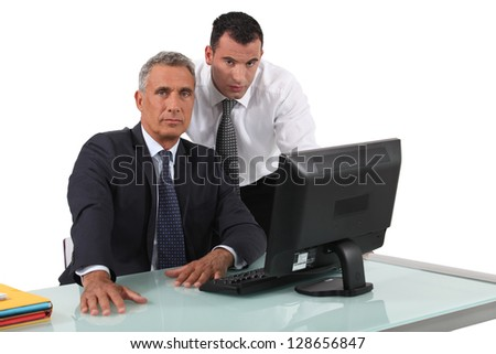 Office workers in front of a desktop computer - stock photo