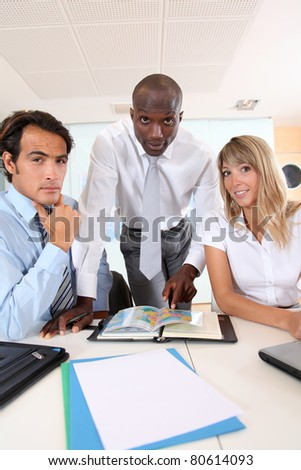Office workers sitting around meeting table - stock photo
