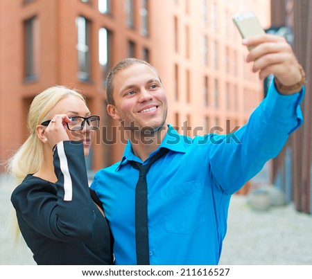 Office workers taking selfie with cellphone. - stock photo