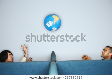 Office Workers Tossing Globe - stock photo