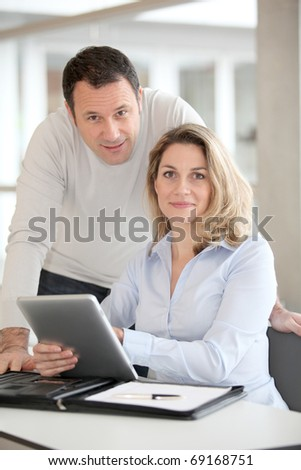 Office workers using electronic tab in the office - stock photo