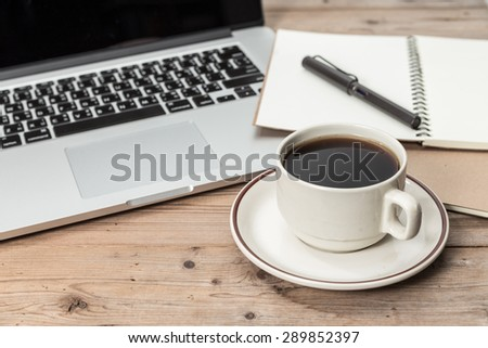 office working desk top view with laptop, notepad and coffee - stock photo