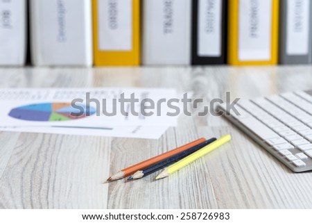Office working place on wooden table. Workspace on light beige wooden table with colored pencils, computer keyboard, printed charts and stack of folders - stock photo
