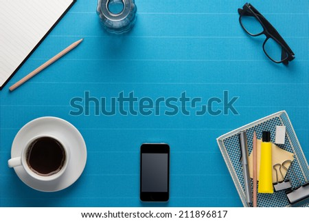 Office workplace,office Equipment and coffee break on blue crepe paper desk  - stock photo