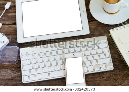 office workplace - phone  on keyboard with tablet, copy space on blank screen - stock photo