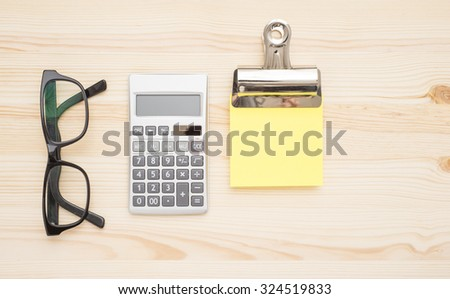 Office workplace with blank memo note, calculator and glasses. - stock photo