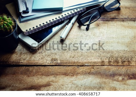 Office workplace with digital smartphone pen notepad and green plant. Creative studio concept - stock photo