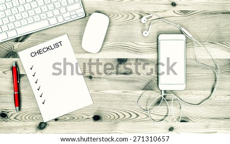 Office Workplace with Keyboard, IPhone, Headphones, Stationary and Office Supplies. Mock Up Check List. Retro style toned picture - stock photo
