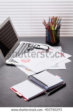Office workplace with laptop, reports and pencils on desk table in front of window with blinds - stock photo
