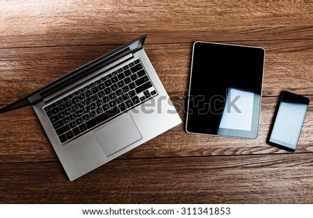 Office workplace with open laptop, tablet pc, phone  on wooden desk  - stock photo