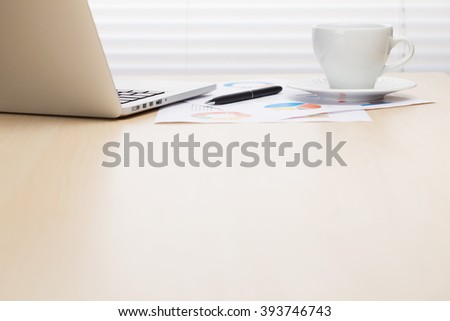 Office workplace with with laptop and coffee on wooden desk table in front of window with blinds. Focus on cup. View with copy space - stock photo