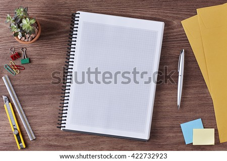 Office Workspace. Top View of a Business Workplace. Wooden Desk Table, Paper Cutter, Ruler, Pen, Post it, a Blank Notebook, Envelope, Plant Pot, Clips. Copy space for text or Image - stock photo