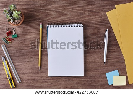 Office Workspace. Top View of a Business Workplace. Wooden Desk Table, Paper Cutter, Ruler, Pen, Pencil, a Blank Notebook, Envelope, Plant Pot, Clips. Copy space for text or Image - stock photo