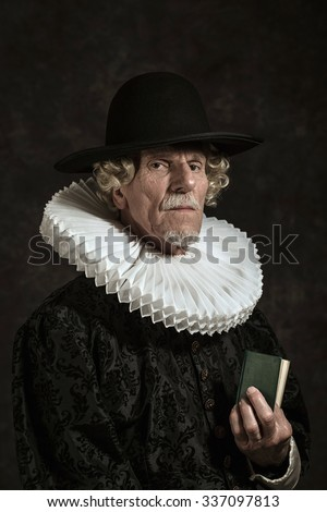 Official portrait of historical governor from the golden age. Holding a book. Studio shot against dark wall. - stock photo