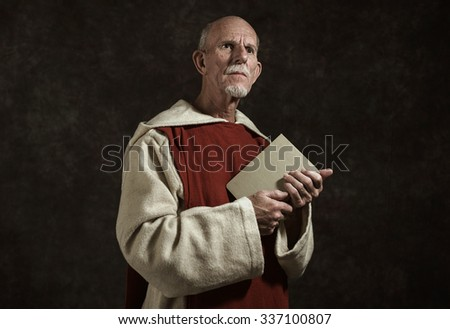 Official portrait of monk holding book. Studio shot against dark wall. - stock photo