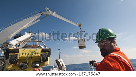 Offshore crane lifting operations - men attending tag lines - stock photo