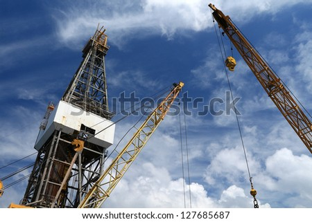 Offshore Drilling Rig with Working Cranes on Cloudy Day - stock photo