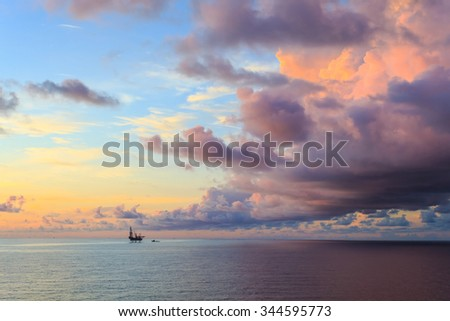 Offshore jack up drilling rig in the middle of the ocean during sunset time - stock photo