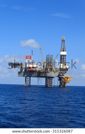 Offshore Jack Up Drilling Rig Over The Production Platform in The Middle of The Sea - stock photo