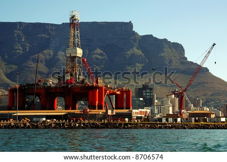 offshore oil extraction rig in bay into a big city near mountains. cape town, south africa - stock photo