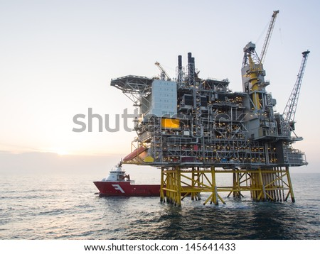 Offshore oil platform with a supply vessel on the North Sea, in the Norwegian sector - stock photo