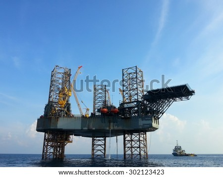 offshore oil rig drilling platform and small ship with blue sky - stock photo