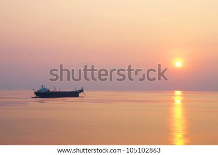 Offshore Oil Tanker and Small Crew Boat in The Offshore Oil and Gas Production Field at Sunset Time - stock photo