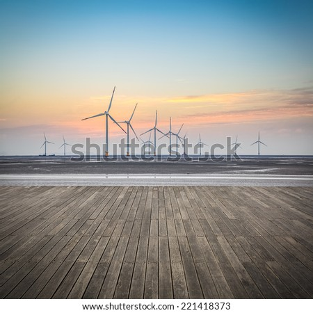 offshore wind farms in sunrise with wooden floor , renewable energy background.  - stock photo