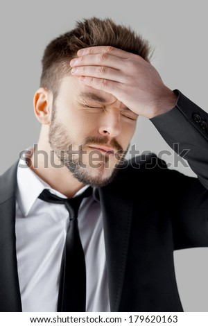 Oh no! Portrait of frustrated young man in formalwear holding hand in hair and keeping eyes closed while standing against grey background - stock photo
