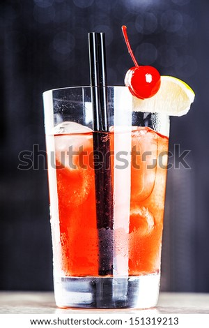 ohol tequila sunrise or margarita cocktail with crushed ice, green mint, yellow straws, lime in small glass isolated on white background - stock photo