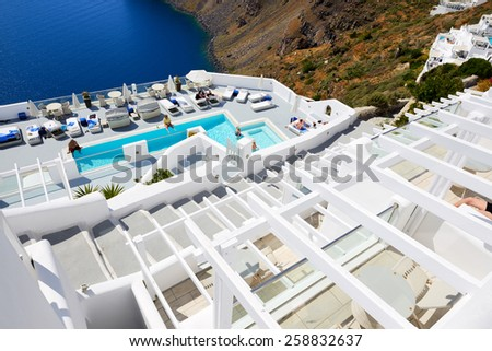 OIA, GREECE - MAY 17: The tourists enjoying their vacation at luxury hotel on May 17, 2014 in Oia, Greece. Up to 16 mln tourists is expected to visit Greece in year 2014. - stock photo