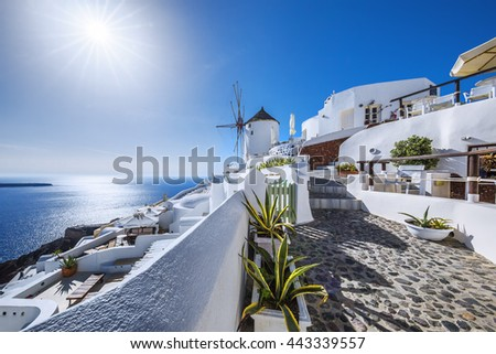 Oia, Greece - May 31, 2016 : View of Oia, one of the most beautiful places in Santorini at sunset. Famous windmill in the background. - stock photo