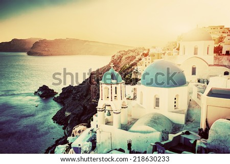 Oia town on Santorini island, Greece at sunset. Traditional and famous churches with blue domes over the Caldera, Aegean sea - stock photo