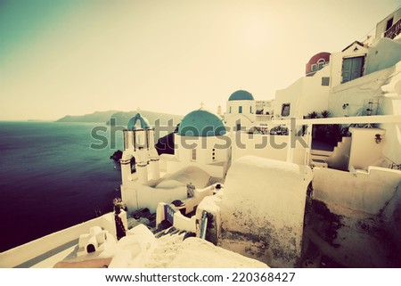 Oia town on Santorini island, Greece at sunset. Vintage, retro style. Traditional and famous churches with blue domes over the Caldera, Aegean sea - stock photo