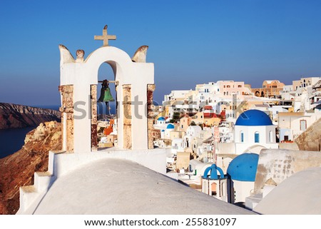Oia Village Santorini, focus Bell tower with blue domes in background.  - stock photo