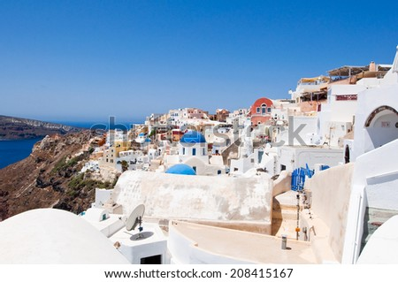 Oia with typical white and blue painted houses on the island of Santorini, Greece. - stock photo
