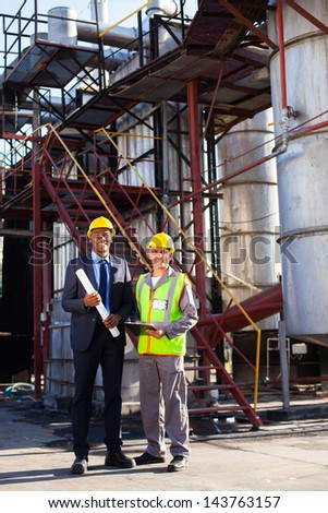 oil and chemical manager standing with factory worker at plant - stock photo