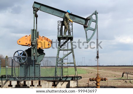 oil and fuel industry oil worker standing on the pump jack - stock photo